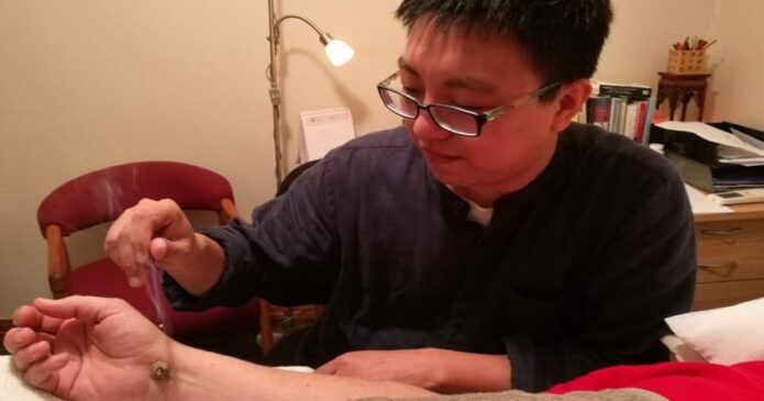 Mike Yin performing chinetsu moxibustion for carpal tunnel